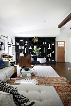 Painting a built in bookcase black might seem like an unlikely room fix. But, as you can see here, the trend works to create distinct spaces — in this case, it cuts off off the living room from the kitchen, which used to flow into each other. Click through to discover more ways to use black built ins — you might just find yourself a weekend project...