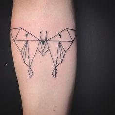 Geometric moth tattoo on a forearm