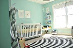 murs en vert d'eau et un tapis à rayures noires et blanches dans la chambre bébé