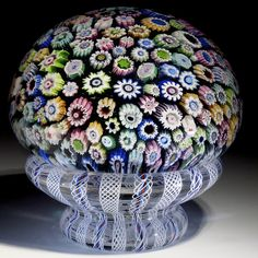 """John Deacons Paperweight: A magnum close pack ball of large millefiori canes set over a translucent Aqua core rests on a latticinio pedestal to form this Piedouche paperweight.  The pedestal is accented with fine White latticinio strips alternating with loose spiral latticinio threads over a Blue/Red/Blue ribbon. Signed with a """"JD """" cane.  2012, 3.5""""w x 3.5t, 30oz"""