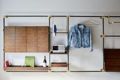 Clever custom wall units are part of every room and include solid walnut drop-leaf desks, storage racks of bronze and brass, and multi-format radios from Revo.