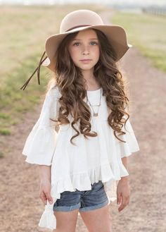 Featuring a ruffled hem and bell sleeves, this dramatic high low top is the perfect bohemian addition to any little girl wardrobe.