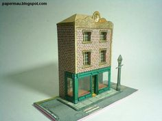 A simple model of a little shop, a two store building. A desktop model in two pages. It measures 11 cm x 7 cm without the base. Download this paper model for free at Papermau.
