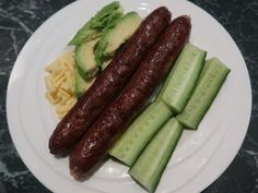 Plate with sausages, cheese, avocado and cucumber