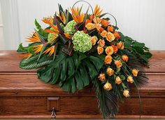 An wide array of impressive birds of paradise and beautiful orange roses make this funeral casket spray a worthy tribute piece. It is nicely complimented by. Arrangements Funéraires, Funeral Floral Arrangements, Church Flower Arrangements, Church Flowers, Funeral Flowers, Deco Floral, Arte Floral, Casket Flowers, Funeral Caskets