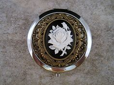"""Handmade Victorian Silver Rose Cameo Compact Mirror. *High quality silver compact mirror *Detailed oxidized silver filigree *Oxidized silver Victorian setting *Detailed rose cameo *Gift box tied with a bow Measures: 3 3/4"""" in diameter."""