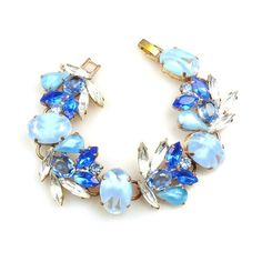 "Blue shades and clear crystal colors charming bracelet, length of bracelet 7.00"", width 1.10"". Price: $32.90"