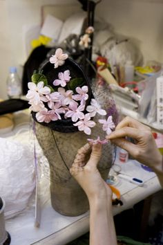 Milliner Mitsumi Kinoshita applying flowers to a veiled hat at Stephen Jones Millinery, Covent Garden 2008 (copyright V&A Images) Millinery Hats, Fascinator Hats, Fascinators, Headpieces, Silk Flowers, Fabric Flowers, Stephen Jones, Cocktail Hat, Diy Hat