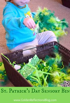 St. Patrick's Day sensory bin using feathers, garland, and green easter grass   www.GoldenReflectionsBlog.com