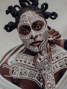 Laolu Senbanjo creating a body painting on the actress Danielle Brooks in his Brooklyn studio in November. Credit Sasha Arutyunova for The New York Times