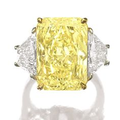 Fancy Intense Yellow Diamond weighing 13.88 carats, flanked by two trapeze-shaped diamonds together weighing approximately 3.00 carats, mounted in platinum and 18 karat yellow gold sold by Sotheby's for $470,000