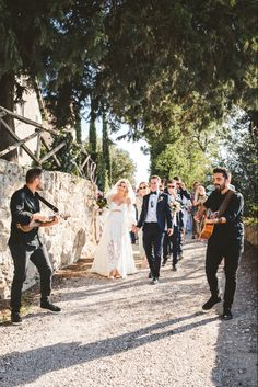 Bride and groom followed by all guests the church after the wedding at Borgo di Tragliata