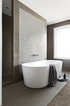 Every space needs a focal point and the geometric tiles behind this freestanding bath make for a great feature wall.