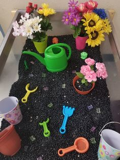 Garden Sensory Bin - Black beans, dollar store pots & flowers, a Wal-Mart water can, sand shovels & hoes.  (I ended up sawing about 2 inches of the watering can's spout off to allow the beans to flow better.)