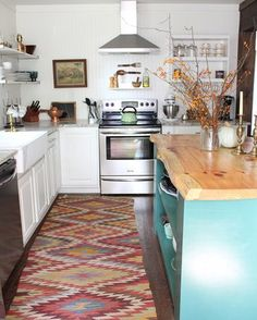 A white bohemian kitchen with a southwestern style rug, a teal island, and natural accents.