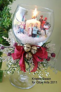 Christmas Candle Votive Holder~~ GlueArts Designer: Kristen Swain Supplies: Hot Glue Gun & Glue Sticks Dollar Store Wine Glass Village Figurines Cap from Starbucks Iced Coffee Bottle Craft store snow flake Craft store bells/stems/berries Ribbon Candle Votive 1. Fill glass with Flake Snow. 2. Hot glue figurines around lid, place inside glass. 3. Hot Glue stems to front of glass. 4. Tie bow with Ribbon, stick to stems, then stick 3 bells to center of ribbon bow, using hot