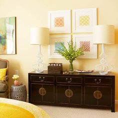 Artwork gives this yellow master bedroom an opportunity to expand beyond a tonal color palette and also adds pattern and texture. Here, modest-size pieces form a grid to fill the space over the sideboard.