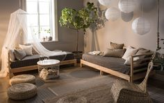 A living room in natural colors and decorated with day beds, paper lamps, woven cushions and plants.