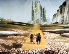 Still photo of Emerald City from 1939 film The Wizard of Oz. Photo courtesy totalfilm.com  :: The Wonderful Wizard of Oz by L. Frank Baum was a best selling book in the year 1900.  It appeared as a stage play in 1902 under the simplified name The Wizard of Oz. And the 1939 Warner Brothers movie adaptation, starring Judy Garland with Bert Lahr, Jack Haley and Ray Bolger, and featuring a magnificent music score by Harold Arlen and Yip Harburg, remains an icon of pop culture.