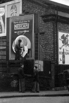 A billboard 'paster' works to complete an advert in Chalk Farm Road, Camden 1957