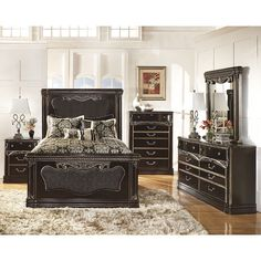 The Hopedale Bedroom Set by Ashley Furniture embraces the elegant beauty of Old World design with the luminous dark black finish highlighted with a pearlized champagne undertone which is beautifully accented with the scrolling carved details and the stylishly shaped padded upholstery with welting details.