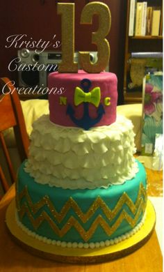 Beautiful cake by Kristy's Custom Creations for 2 friends celebrating their 13th birthday together. Bottom tier: chocolate cake w/ buttercream icing. Middle tier: yellow & chocolate cake alternating layers w/ BC icing. Top tier: yellow/chocolate marble cake w/ BC icing. Tiers are covered in aqua, white & fuchsia marshmallow fondant. Ruffles are mmf & chevron is modeling chocolate w/ gold twinkle dust. Anchor, bow & letters are also modeling chocolate. Wooden 13 topper is painted w/ gold…