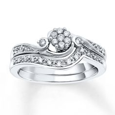 A floret of round diamonds is flanked with a single round diamond on either side as the focal point of this elegant bridal set for her. Graceful tendrils of round diamonds set in 10K white gold and hemmed with milgrain unfurl along each side of the engagement ring, and along the matching wedding band. The set has a total diamond weight of 1/5 carat. Diamond Total Carat Weight may range from .18 - .22 carats.