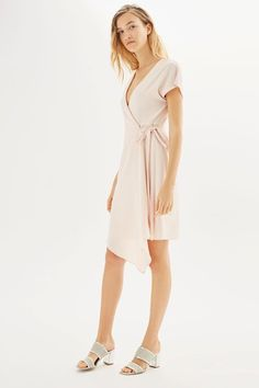 Summer styling couldn't be any easier than this chic wrap dress in blush. Detailed with a plunge v-neckline, modern asymmetric hem and belt detail to cinch in the waist. Finish the look with heeled mules for a day to night feel.