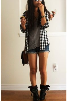 jean shorts, light grey tank top, black and white plaid shirt open over it, and boots.