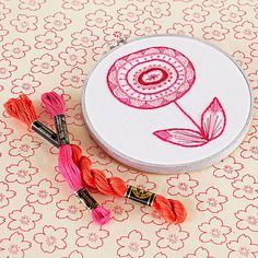 Pretty in pink and bursting with stitch goodness, this funky blossom comes to life with rings of highly textured embroidery. Designed by Sarah Hennessey.
