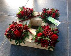 Vierkant bloemstuk met rode rozen en Cornustakken.