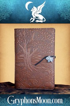 Creekbed Maple Leather Journal - A regal maple spreads its branches over a rushing stream. Captivating wraparound scene continues on around to the back of the journal. A delight to the eye and hand, it is ideal for use as a diary, travel or dream journal, BoS, or for sketching, notes, and appointments. Made from top-quality leather. Refillable. #Journal #LeatherJournal #MapleTree #MapleLeaf #Diary #BookOfShadows #Spellbook #Writer #Poetry #Notebook #Planner Saddle Leather, Leather Tooling, Refillable Journal, Moon Logo, Dream Journal, Art Supply Stores, Great Father's Day Gifts, Blank Book, Leather Journal