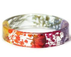 Please allow approximately 1-2 weeks processing time   MEASUREMENTS- 5/8 inch wide with 2 5/8 inner diameter *Available In This Size Only  **************************************************************************​  This lightweight Slip on Bangle is made with Real Dried rainbow colored flowers Embedded into Crystal Clear Resin and Shaped into a unique and stylish bangle with Glassy finish that sparkles in the light.  Our artisan bangles are created by hand and not by a machine so t...
