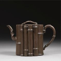 An Yixing Teapot And Cover. Qing Dynasty, Kangxi Period    the body modelled in the form of multiple vertical stems of bamboo, set to one side with a similarly modelled spout and to the other with a loop handle, the flat cover with a leafy twig finial. 12cm., 4 3/4 in