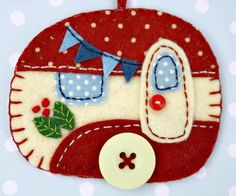 Vintage caravan trailer hanging ornament, handmade from felt and decorated with fabric scraps. With tiny felt bunting and buttons for the wheel and door knob. Colors are vintage red and cream. A perfe