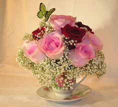 A Dainty Teacup Flower Arrangement minus the butterfly.  On guest book table.