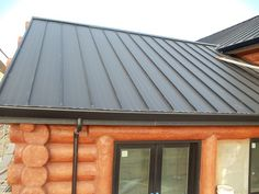 Standing seam metal roofing system installed on a log house in California.