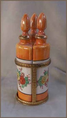 Vintage Lusterware perfume set consists of three porcelain bottles. The bottles are triangular in shape and feature Asian flowers in hues of Yellow, Orange and Green with Black accents. They sit in a Gold metal embossed caddy.
