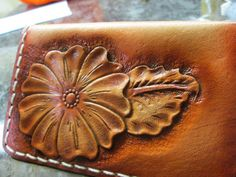 Womens floral leather business card case, wallet, Western styling with Sheridan tooling with flowers and foliage. It is a sharp piece finished in my fav British Tans then poly coated as a resist and highlighted to obtain that extra depth. Then top finished the entire piece with the same poly coat to guarantee years of beauty and service. In total its been hand cut, hand tooled, oiled, edges beveled, colors airbrushed, hand stitched in Arctic white waxed linen thread, then edges fully…