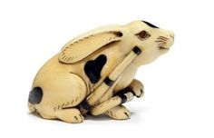 An Ivory Netsuke   Signed Hidemasa, Edo Period (18th-19th century)   Of a piebald hare, black lacquer details, eyes inlaid in cowhorn