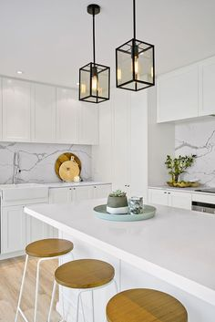 Stunning hamptons style kitchen by Three Birds Renos!!Love the sleek white cabinetry with marble look back splash and black pendant lights