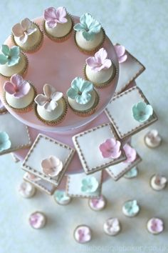 using the same sugar pastel decorations on various sweets, like sugar cookies, cupcakes and mini cakes.