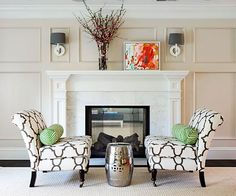 Paneled walls and a marble fireplace surround set a classic tone in the living room, but graphic fabrics—including zebra-print bolsters on the slipper chairs—keep the look fresh.