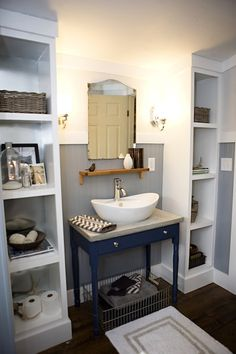 navy blue sink console, concrete countertop, white vessel sink, polished nickel faucet, wire basket, industrial wire basket,