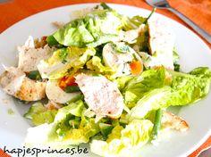Caesar salade met kip bestaat traditioneel uit de typische caesar dressing, kip, broodcroutons en parmezaan.