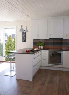 KJØKKENHALVØY: Den hvite kjøkkeninnredningen er freshet opp med et stripete tapet fra Borge.