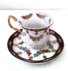 Vintage     Footed Teacup and Saucer   GNA    Fine Porcelain    Gold Trimmed Cup and Saucer.  Floral Design   Pinks Blues and Greens