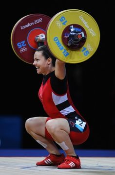 Christine Girard of White Rock, B.C., smiles as she prepares to lower the barbell after winning the bronze medal in the women's 63-kilogram weightlifting final at ExCeL Arena. July 31, 2012