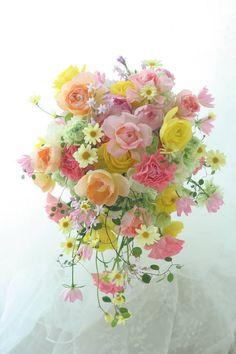 中央から、ふんわり広がるように形作るブーケを一会ではシャワーブーケと呼んでいます。新婦様がお好きと言ったいくつかのお花のうち、マーガレットだけ会場装花の中...