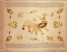 "Rectangular linen table cover with the center panel embroidered in polychrome silks and an ivory drawn work border sewn to all four sides. The embroidery depicts a large ""bicho"" or beast in pink, blue and gold, suckling two small beasts, with a third small beast inside the mother beast; four small beasts are scattered around. In each corner, an owl with a gold face and a pink and blue checkered body, and at each side, a double-headed bird in gold and blue. In the center panel above and below…"